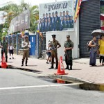 Police and army personnel stand watch