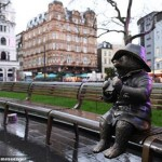 Leicester Square in London: Paddington perched eating a sandwich on a bench