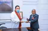 Prof. Karunadasa presents new book to PM
